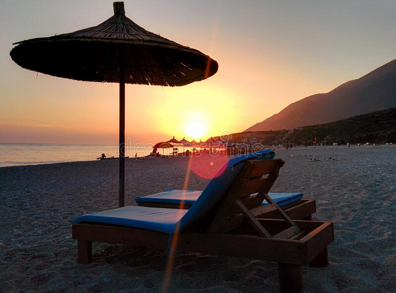 Brown Wooden Lounger on Seashore during Day Time royalty free stock images