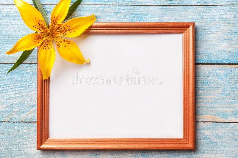 Brown wooden photo frame with yellow flowers lily on old blue shabby background royalty free stock image