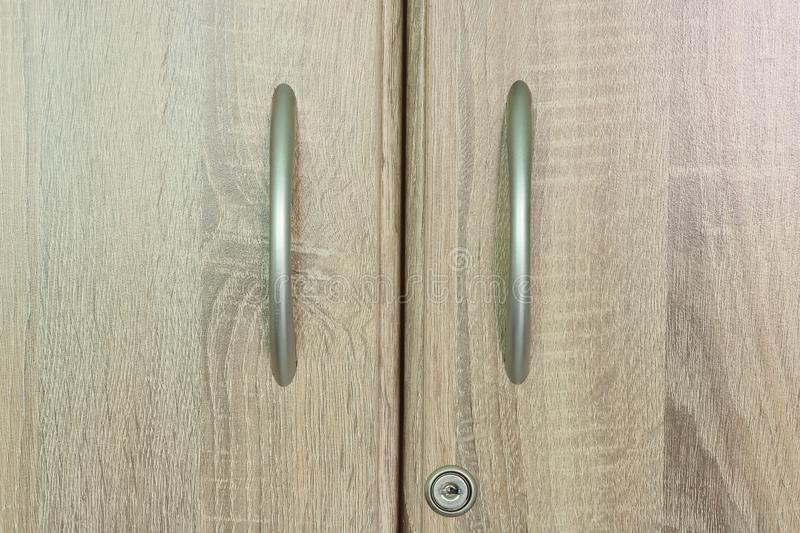Brown wooden wardrobe drawer with one keyhole.  stock photography