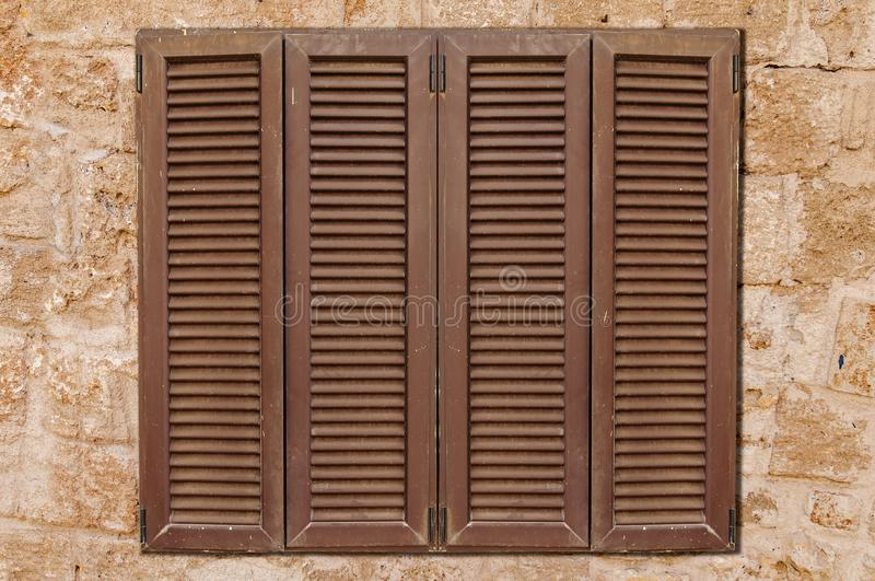 Brown wooden window on yellow castle old stone pattern texture. Wall close stock photo