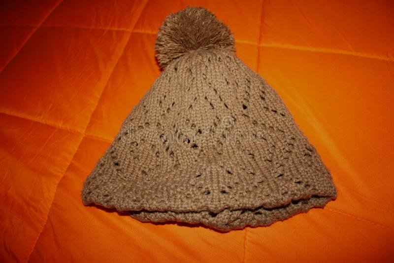 Brown wool hat or cap, knitted. resting on a bright orange blanket stock photo