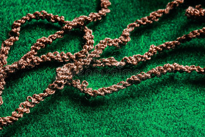 Brown woolen threads on a green background. Brown woolen threads on a green fabric background stock photography