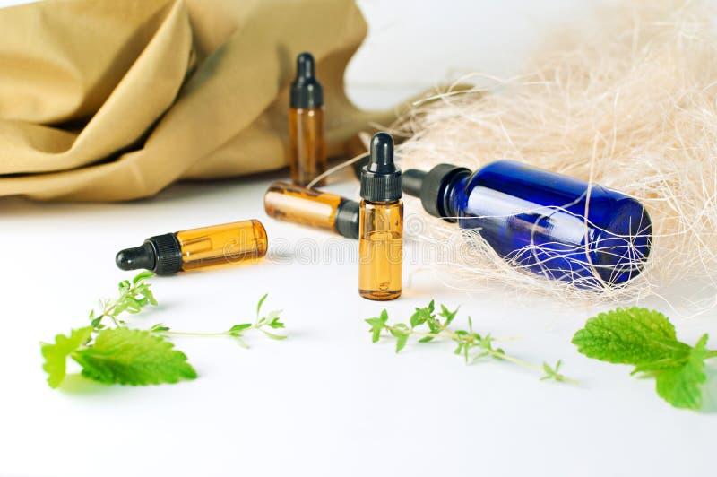 Brown y botellas azules de aceite esencial con la menta fresca y el thym imagen de archivo