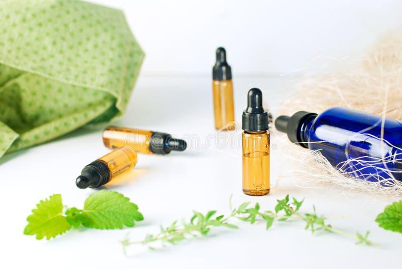 Brown y botellas azules de aceite esencial con la menta fresca y el thym fotografía de archivo