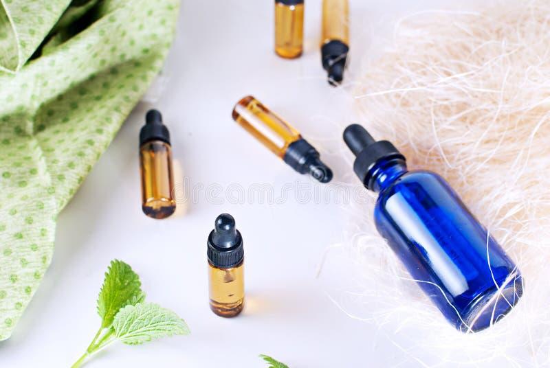 Brown y botellas azules de aceite esencial con la menta fresca en blanco foto de archivo libre de regalías