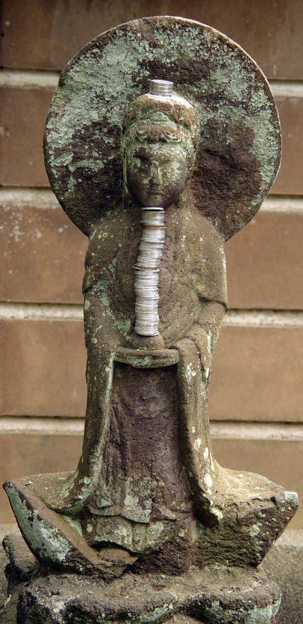 Brown y el gris tallaron a Buda de piedra con una pila de monedas y de un halo grande imagenes de archivo