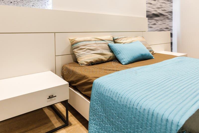Brown y linos azules en cama en dormitorio acogedor imágenes de archivo libres de regalías