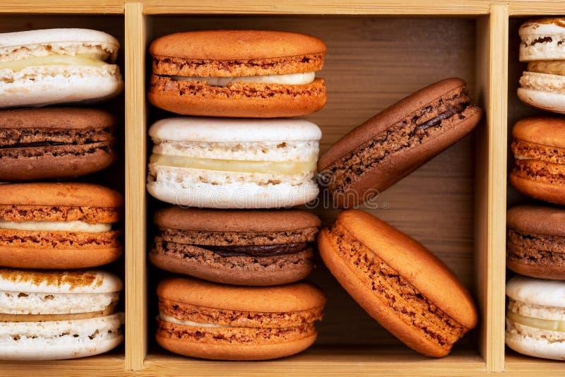 Brown y macarons o macarrones franceses blancos, chocolate, café, caramelo y vainilla apilados en una caja de bambú foto de archivo libre de regalías