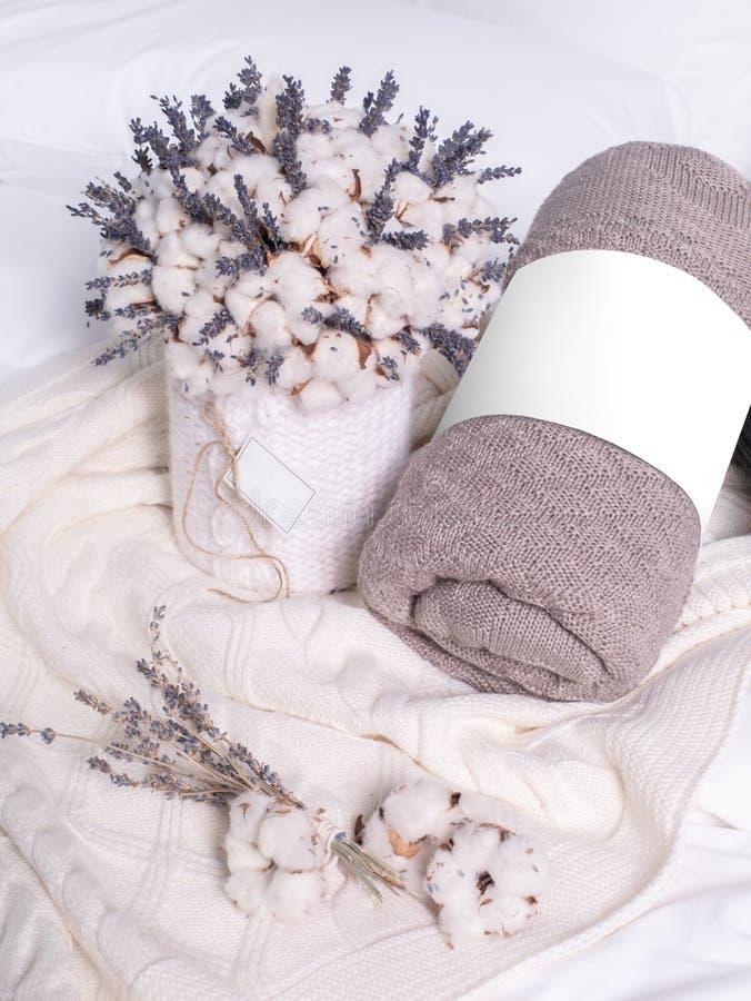 Brown y telas escocesas blancas en la cama y las flores imagenes de archivo