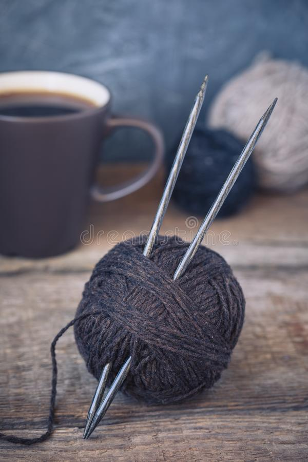 Brown yarn ball with knitting needles on a rustic wooden background, wabi sabi style stock photo