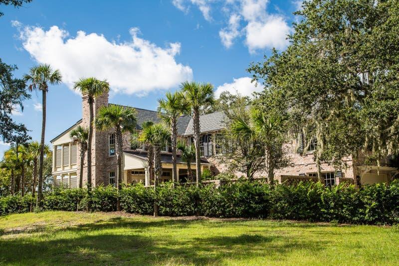 Brown-Ziegelstein-Villa mit Palmen unter blauem Himmel stockfotos