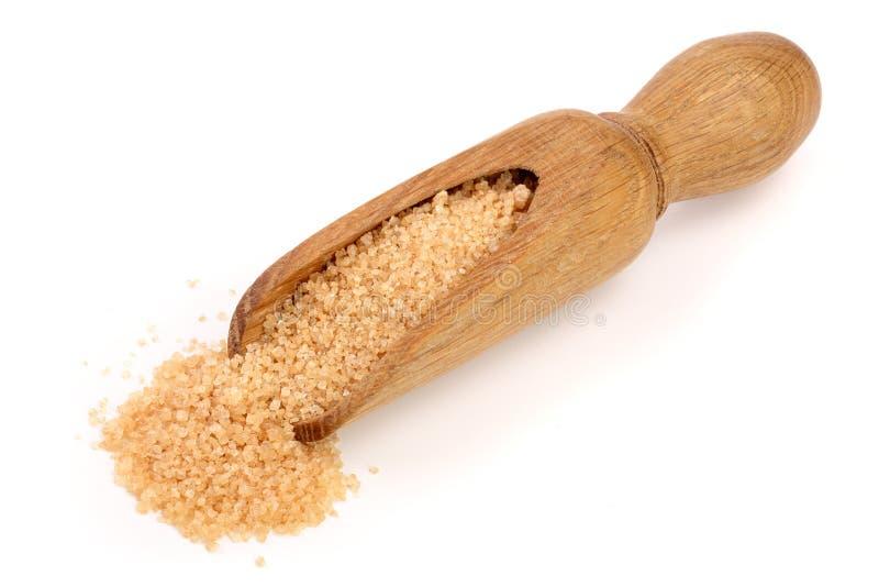 Brown-Zucker in der hölzernen Schaufel lokalisiert auf weißem Hintergrund lizenzfreies stockbild