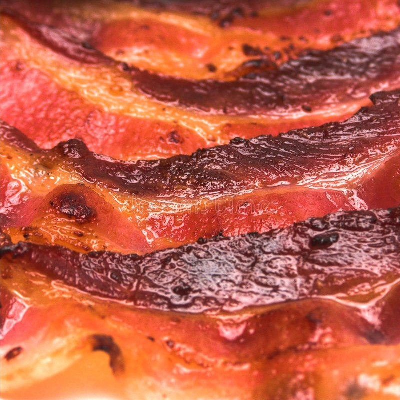 Browned Bacon. An extreme closeup view of some nicely browned bacon strips stock photos