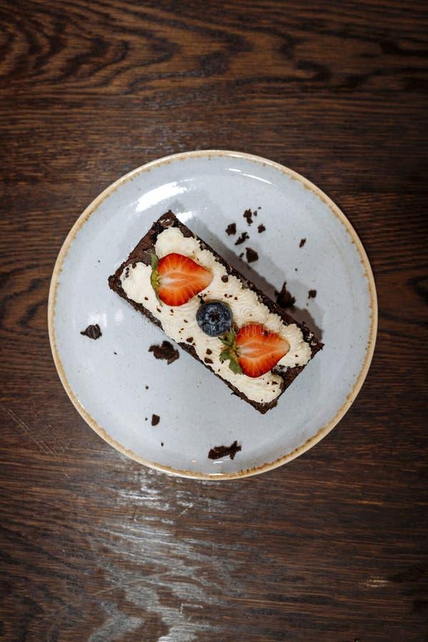 Brownie που διακοσμείται με την κτυπημένα κρέμα, τις φράουλες και τα βακκίνια σε ένα πιάτο σε ένα σκοτεινό ξύλινο υπόβαθρο στοκ φωτογραφία