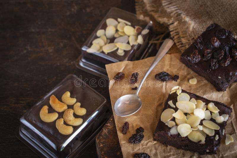 Brownie cake with almond slices placed on paper and wood there are spoon, same object, brownie in package and currant placed stock photography