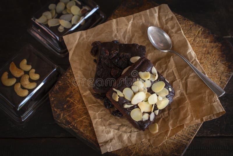 Brownie cake met amandelmoten op papier en hout daar is lepel, blauw in een verpakking en kromme die om zich heen wordt geplaatst stock afbeeldingen