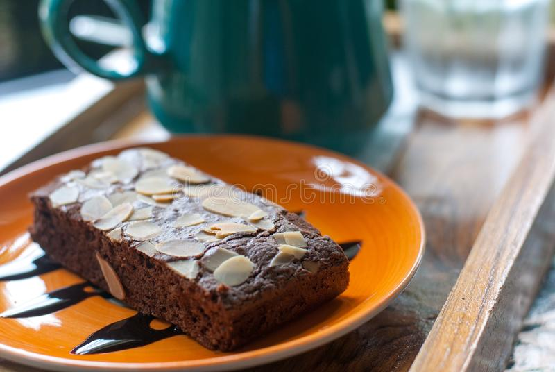 Brownie cake with sliced nut on orange ceramic plate placed in front of coffee mug. Ready to eat stock photos