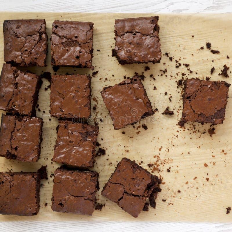 Brownie casalinghi del cioccolato su uno strato bollente su una superficie di legno bianca, vista superiore Disposizione piana, s immagine stock libera da diritti