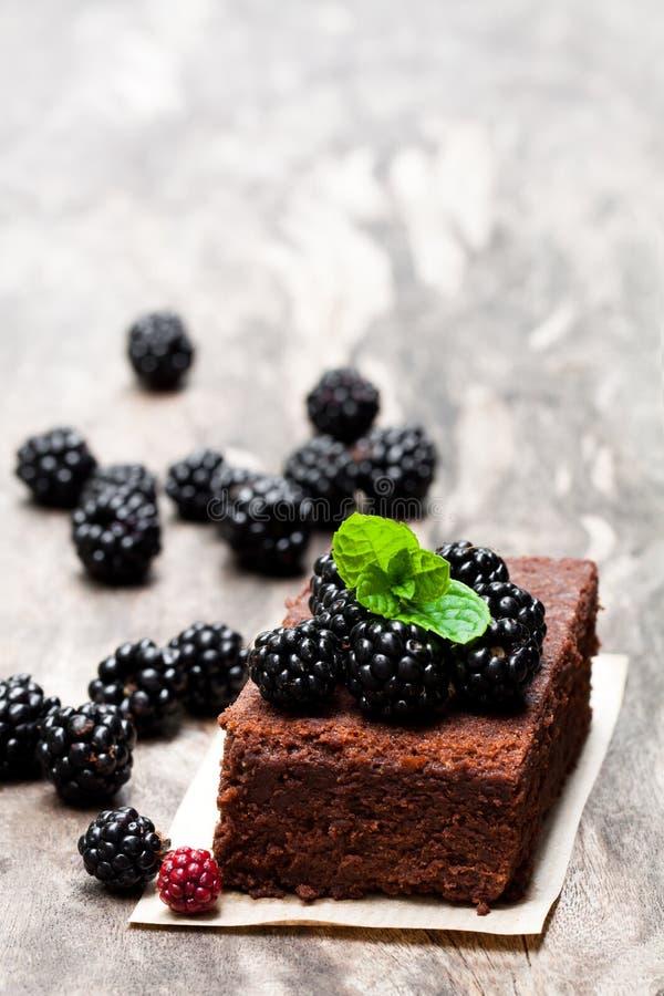 Brownie casalingo del cioccolato con le bacche sulla tavola di legno fotografie stock libere da diritti