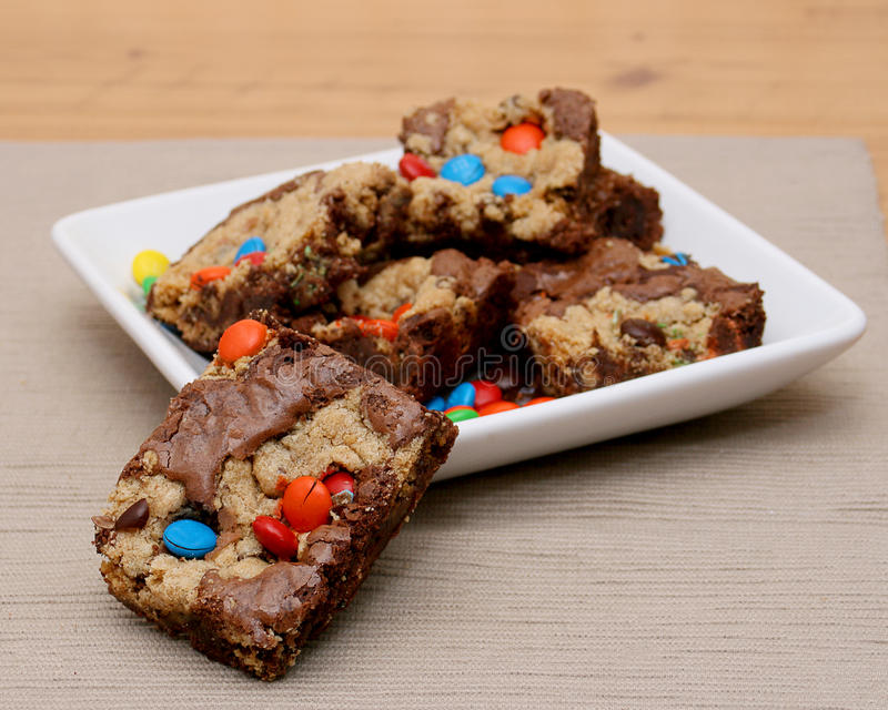 Brownie Cookie Bar. Single brownie cookie bar leaning on a plate full of more brownie cookie bars with chocolate candies in it royalty free stock photo
