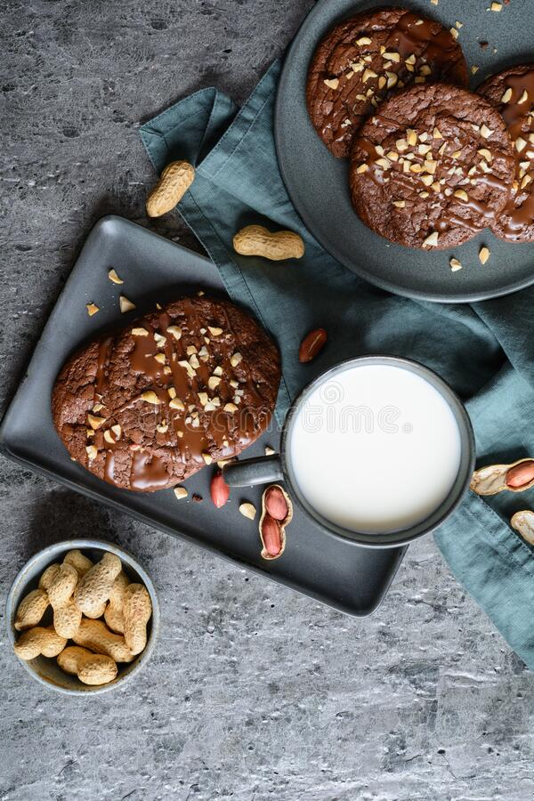 Brownie cookies topped with melted chocolate and chopped peanuts. Delicious brownie cookies topped with melted chocolate and chopped peanuts stock photo