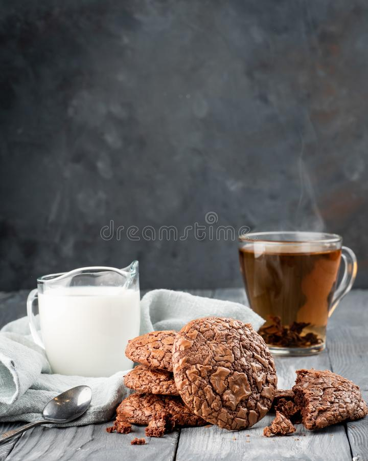 Brownie cookies on a wooden table with tea and milk. Copy space stock photography