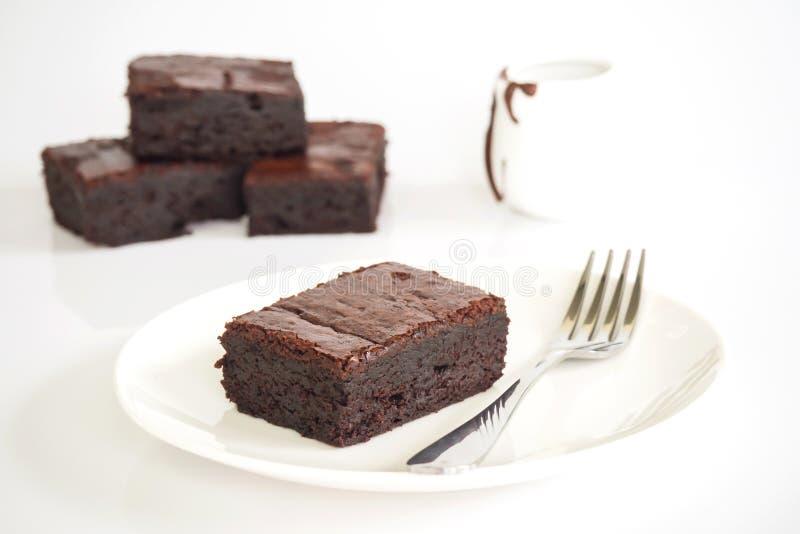 Brownie cortados en la placa blanca Servido con el topp de la pasta dura de chocolate fotos de archivo libres de regalías