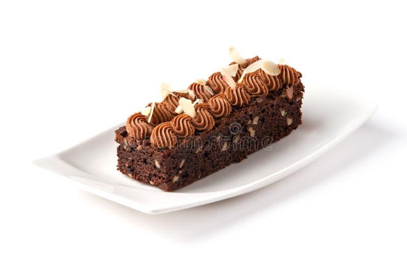 Brownie decorada com os flocos do creme e da amêndoa do chocolate em uma placa branca em um fundo branco isolado foto de stock royalty free