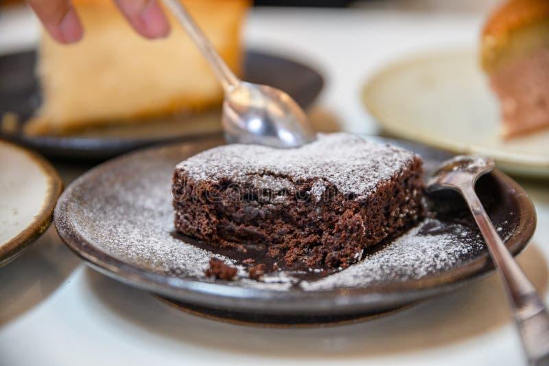 Brownie del chocolate de la cuchara que saca con pala con la congelación del polvo foto de archivo