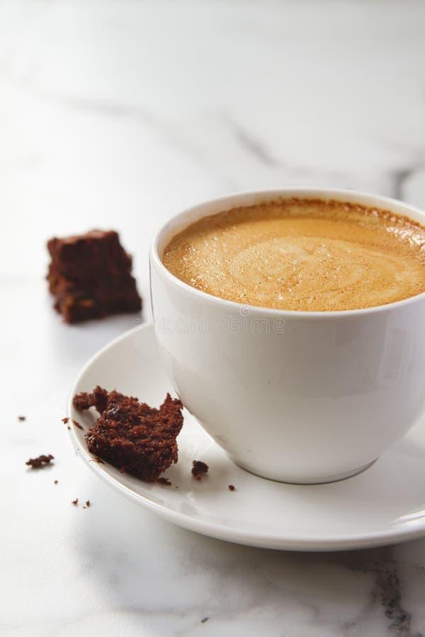 Brownie del chocolate que desmenuza en la taza y el platillo de café del latte foto de archivo