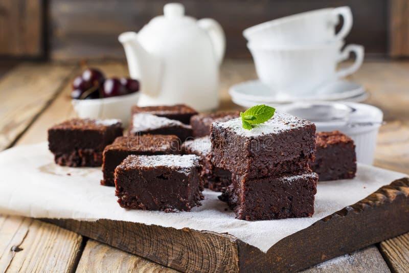 Brownie del cioccolato con zucchero e le ciliege in polvere su un fondo di legno scuro fotografia stock