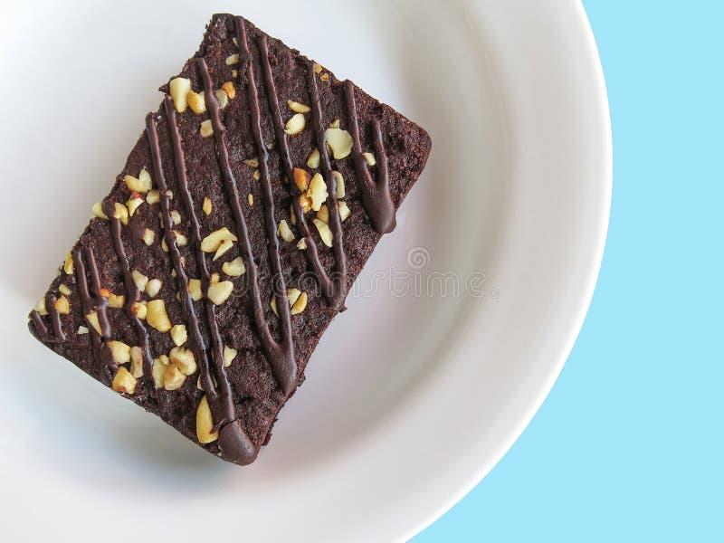 Brownie del cioccolato su un piatto bianco, vista superiore Priorità bassa per una scheda dell'invito o una congratulazione immagine stock