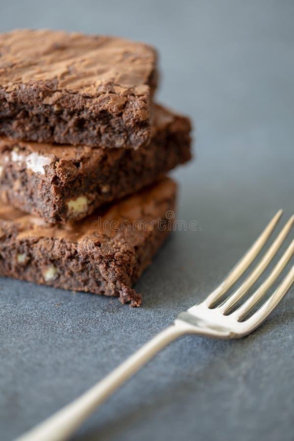 Brownie del cioccolato in un mucchio di tre con la forcella d'argento immagini stock libere da diritti