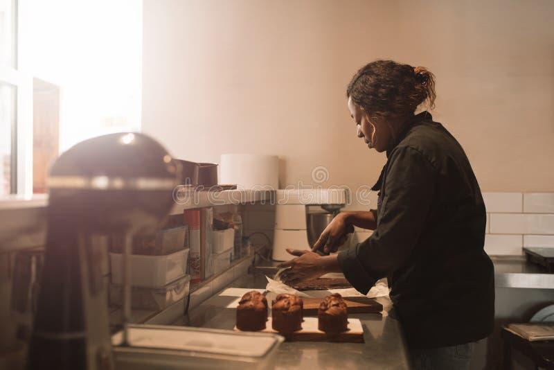 Brownie del corte del panadero en el contador de una cocina comercial fotografía de archivo