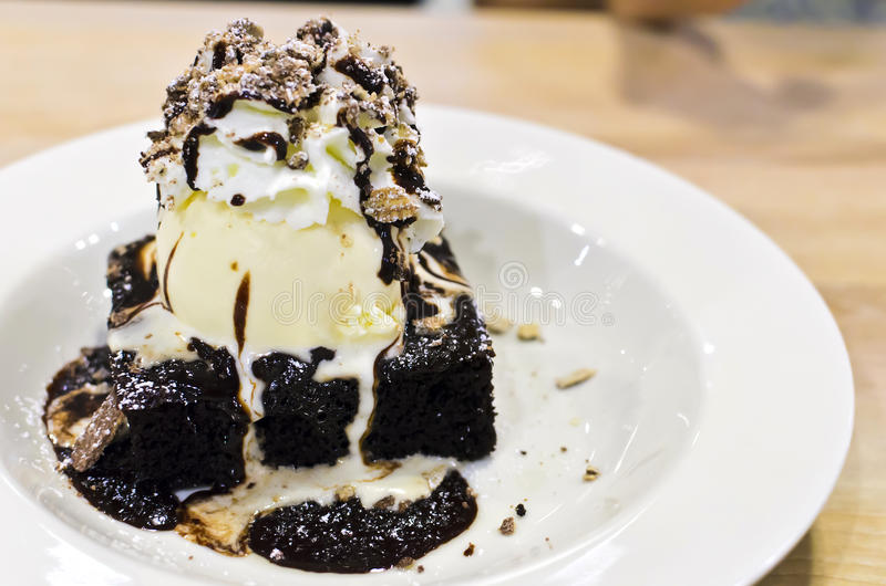 brownie dessert on a white plate with chocolate syrup and vanilla ice cream.pecans on the top. royalty free stock photos