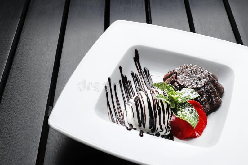 Brownie do chocolate com gelado e morangos em um de madeira preto imagens de stock royalty free
