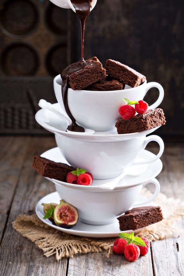 Brownie en tazas de café apiladas con la salsa de chocolate fotos de archivo
