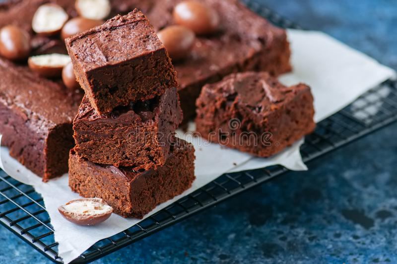 A brownie escura do chocolate esquadra em uma cremalheira de fio decorada com o cre imagem de stock