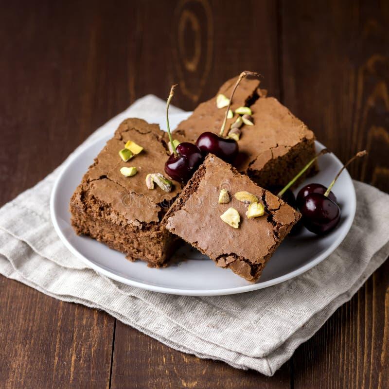 Brownie hecho en casa sabroso del chocolate con las nueces en una placa blanca del fondo de madera de la servilleta de lino fotos de archivo