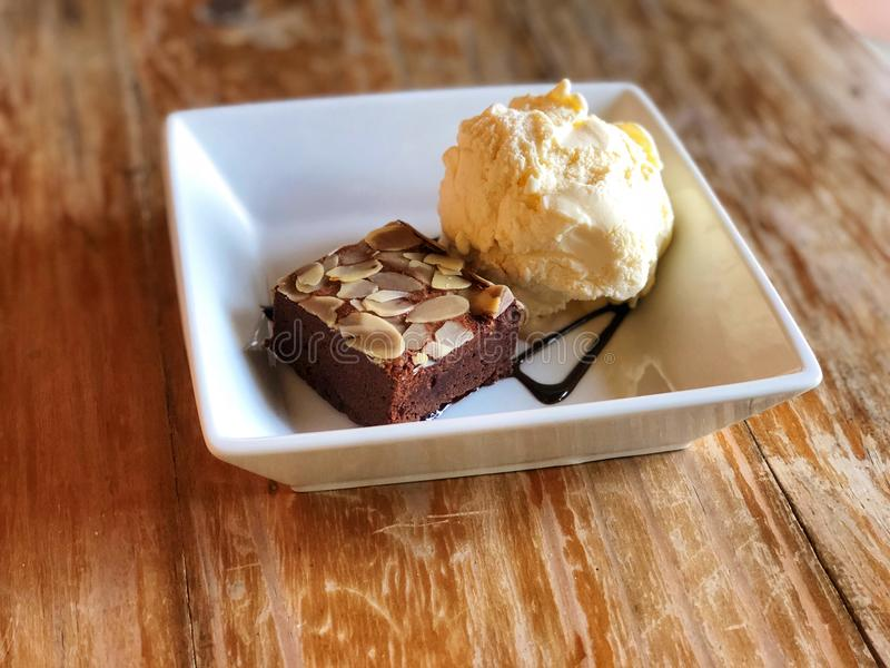 Brownie and ice cream in white square dish on the wooden table royalty free stock images