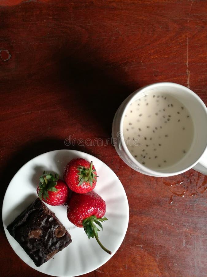 Brownie met aardbeien en een kop van sojamelk stock fotografie