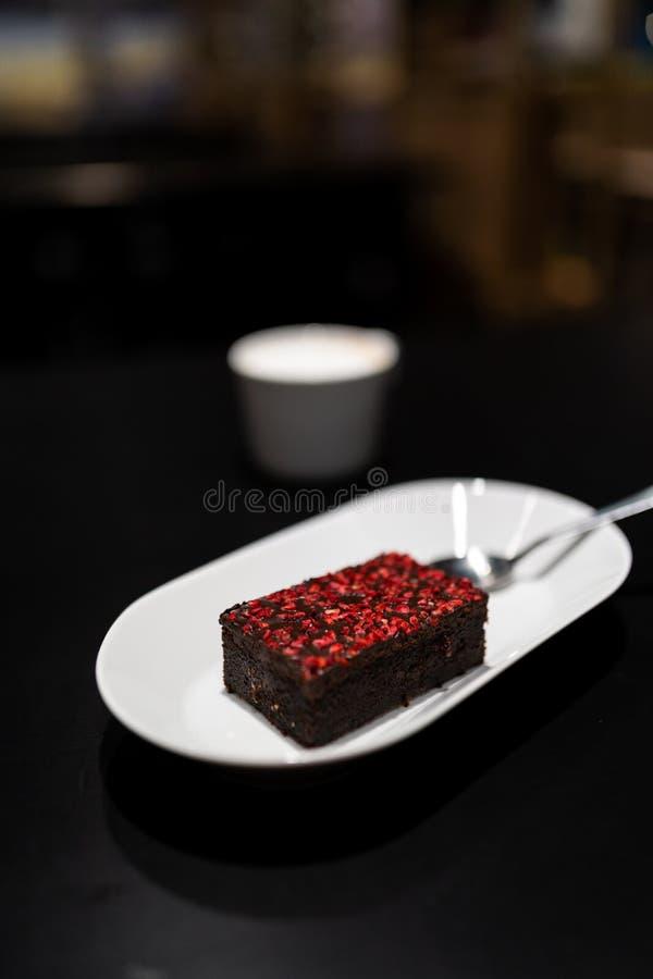 Brownie met met levendige rode droge frambozenkruiden met een kop van cappuccinokoffie op de achtergrond stock afbeeldingen