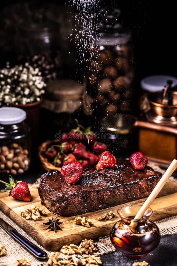 Brownie in sciroppo di cioccolato con le fragole Sugar Snow immagini stock libere da diritti