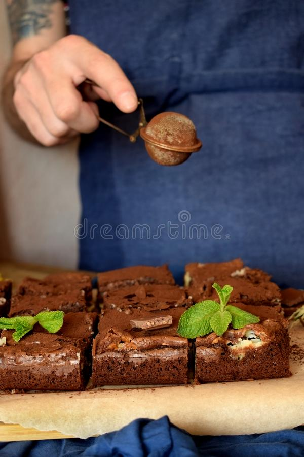 Brownie square pieces decorated with mint and a confectioner royalty free stock photography