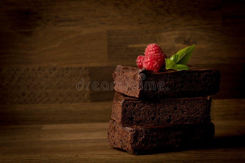 Brownies, εύγευστος που συσσωρεύεται brownies με τα σμέουρα που απομονώνονται στο ξύλινο υπόβαθρο, στοκ φωτογραφία