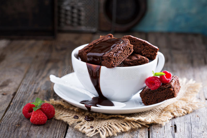 Brownies στα συσσωρευμένα φλυτζάνια καφέ με τη σάλτσα σοκολάτας στοκ εικόνες