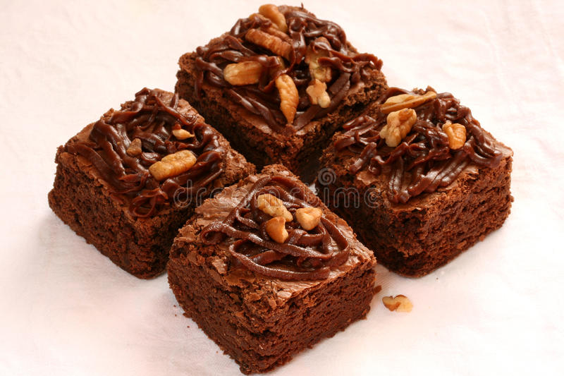 Brownies. Fudge brownies with frosting and nuts royalty free stock images