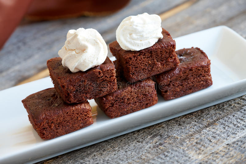 Brownies. Little soft chocolate brownies with white meringue on top served in elegant style stock photos