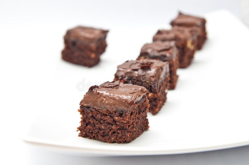 Brownies. Row of brownies cookies with chocolate cream stock photography