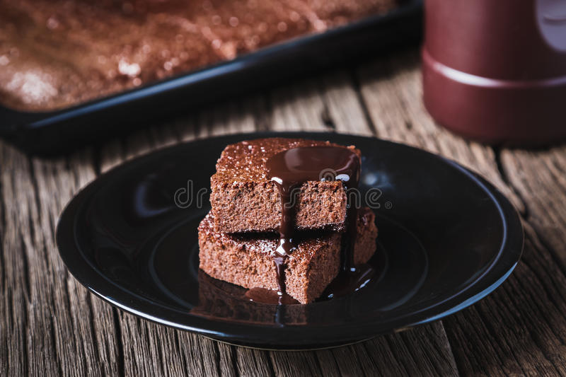 Brownies. Cake chocolate brownies with dark chocolate dressing on wooden table stock image